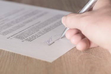 Image of a Person Signing a Contract, Representing Business Law Issues Such as Business Formation, Operation, and Transition; Find Your Business Lawyer in WV (West Virginia), KY (Kentucky), or PA (Pennsylvania) at Hendrickson & Long PLLC.